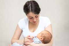 Jonge moeder die haar pasgeboren kind houden Mamma pleegbaby royalty-vrije stock afbeelding