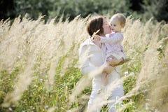 Jonge moeder die haar peutermeisje kust Stock Afbeelding