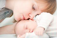 Jonge moeder die haar uitglijdende pasgeboren baby kussen Stock Foto