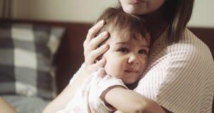 Jonge moeder die haar verstoorde zuigelingsdochter troosten stock video