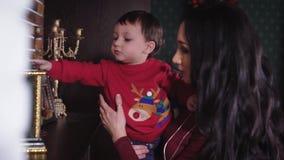 Jonge moeder die haar weinig zoon tonen wat die op een plank boven de open haard liggen De jongen in de rode sweater rekt hand ui stock footage