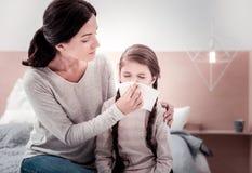 Jonge moeder die haar ziek kind behandelen stock fotografie