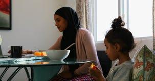 Jonge moeder die laptop met behulp van terwijl haar dochter thuis vruchten 4k eet stock video