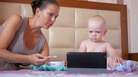 Jonge moeder die leuke baby met een lepel van havermoutpap voeden De babyzitting op het bed en staart beeldverhalen op tabletpc stock video