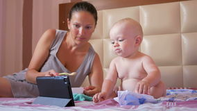 Jonge moeder die leuke baby met een lepel van havermoutpap voeden De babyzitting op het bed en staart beeldverhalen op tabletpc stock footage