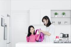 Jonge moeder die meisje voor school voorbereiden Stock Foto's