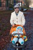 Jonge moeder die met babyjongen loopt in oranje kinderwagen Stock Afbeeldingen