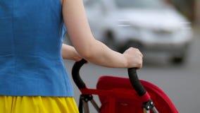 Jonge moeder die met dicht lopen omhoog kinderwagen bij de straat achtermening De moeder met een wandelwagen loopt onderaan de st stock footage