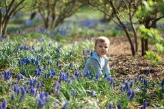 Jonge moeder die met een zoon van de babyjongen op een muscarigebied lopen in de lente - zonnige dag - druivenhyacint royalty-vrije stock afbeeldingen