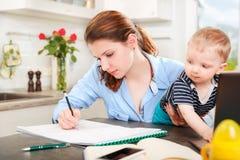 Jonge moeder die met haar baby werken Stock Fotografie