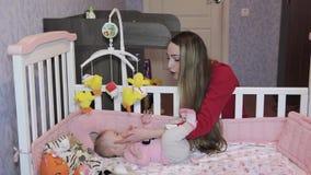Jonge moeder die met haar weinig dochter in bed spelen stock videobeelden