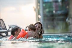 Jonge moeder die met twee jonge geitjes in zwembad genieten van royalty-vrije stock afbeeldingen