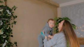 Jonge moeder die op haar babyzoon werpen stock video