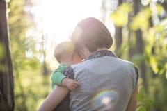 Jonge moeder die van een mooi ogenblik van liefde, tederheid genieten en Stock Foto