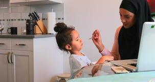 Jonge moeder die voedsel geven aan haar dochter op eettafel 4k stock videobeelden