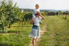 Jonge moeder die weinig jongen een rit op schouders op countrysid geven Stock Afbeeldingen