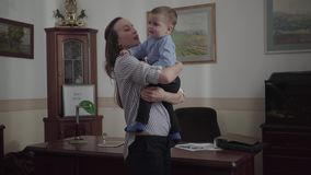Jonge moeder die zich in de moderne bureauruimte bevinden in haar de babyzoon van de huisholding in wapens Het kind is ongehoorza stock video