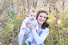 Jonge moeder en babydochter in een park Royalty-vrije Stock Afbeelding