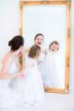 Jonge moeder en dochter bij een spiegel Stock Afbeelding