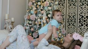Jonge moeder en dochter in de ochtend van het Nieuwjaar op het bed thuis stock videobeelden