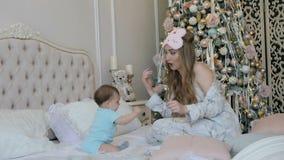 Jonge moeder en dochter in de ochtend van het Nieuwjaar op het bed thuis stock footage