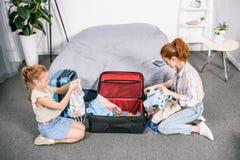 jonge moeder en dochterverpakkingskleren voor reis royalty-vrije stock foto