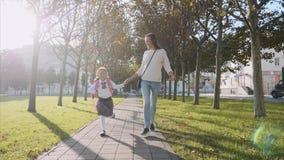 Jonge moeder en een meisje die handen vasthoudt, rennen en glimlachen steadicam, vooraanzicht stock videobeelden
