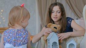Jonge moeder en haar babydochter die togerher thuis spelen stock video