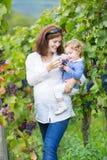 Jonge moeder en haar babydochter in wijnstokwerf Stock Afbeelding