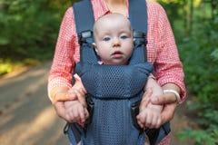 Jonge moeder en haar babymeisje in een babydrager stock fotografie