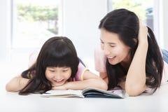 Jonge moeder en haar boek van de dochterlezing royalty-vrije stock afbeelding