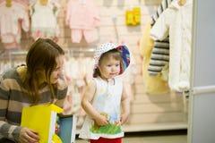 Jonge moeder en haar dochter in de hoed bij de kinderen` s opslag Royalty-vrije Stock Foto's