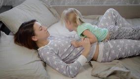 Jonge moeder en haar dochter die in bed en dwaas rond met elkaar in hun weekend liggen Beide meisjes zijn binnen gekleed stock video