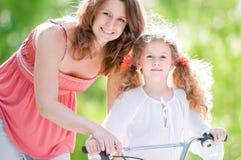 Jonge moeder en haar dochter op fiets Royalty-vrije Stock Afbeelding