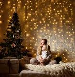 Jonge moeder en haar ittledochters die dichtbij magische Nieuwe jaargiften door een Kerstboom zitten Royalty-vrije Stock Afbeelding
