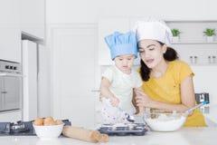 Jonge moeder en haar kind die cake maken royalty-vrije stock afbeeldingen