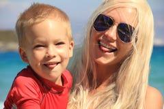 Jonge moeder en haar kind die en pret samen op het overzeese strand spelen hebben in de tijd van de de zomervakantie Gelukkige va royalty-vrije stock fotografie