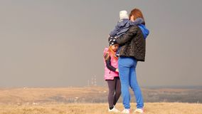 Jonge moeder en haar kinderen in openlucht op mooie de lentedag Moeder en twee kinderen die in het park spelen De pret van de fam stock footage