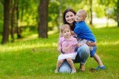 Jonge moeder en haar twee aanbiddelijke kleine jonge geitjes stock foto's