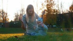 Jonge moeder en haar weinig baby die in de herfstpark spelen Baby die in de camera kijken stock foto