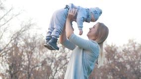 Jonge moeder en haar weinig baby die in de herfstpark spelen Moeder die een baby houdt Heldere hemel royalty-vrije stock foto