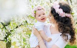 Jonge moeder en haar weinig baby die in een de lenteboomgaard ontspannen Royalty-vrije Stock Foto's