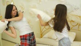 Jonge moeder en haar weinig dochter die met kussens op bed spelen stock videobeelden