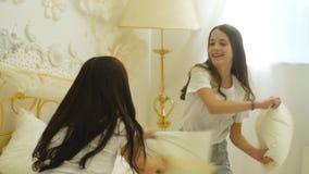 Jonge moeder en haar weinig dochter die met kussens op bed spelen stock footage
