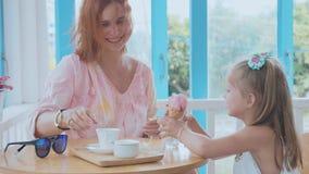 Jonge moeder en haar weinig dochter het besteden tijd in een koffie met roomijs stock videobeelden