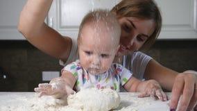 Jonge moeder en haar weinig kind die deeg voorbereiden en bloem op de lijst gieten Weinig baby die met bloem spelen Familie stock videobeelden