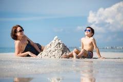 Jonge moeder en haar weinig zoon de bouwzandkasteel bij strand op Florida stock foto's