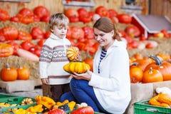 Jonge moeder en haar weinig zoon die op het landbouwbedrijf van het pompoenflard spelen Royalty-vrije Stock Foto