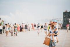 Jonge moeder en haar zoon die in stad lopen Stock Foto