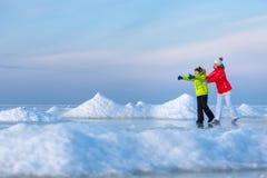 Jonge moeder en haar zoon op ijzig strand stock afbeeldingen